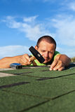 Man fastening bitumen roof shingles with nails and hammer Royalty Free Stock Image