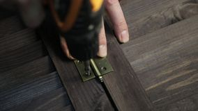 Man is fastening the door hinge to the furniture detail using electric drill.  stock video footage