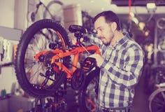 Man fastens bicycle seat Stock Image
