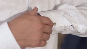 Man fastens buttons on sleeve of the white shirt, man puts on a white shirt. Man fastens buttons on sleeve of the white shirt, man puts on a white shirt stock video