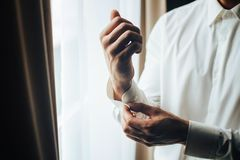 A man fastens with a cufflink on the cuff of the sleeve of a luxurious white shirt. Close up of a man hand wearing a white shirt. And cufflinks. Captures the royalty free stock photo