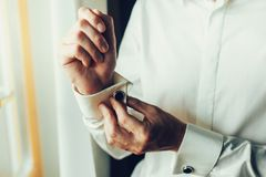 A man fastens with a cufflink on the cuff of the sleeve of a luxurious white shirt. Close up of a man hand wearing a white shirt. And cufflinks. Captures the stock photo