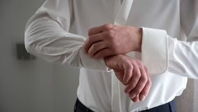 A man fastens cufflinks on a white shirt stock footage