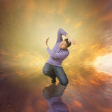 Man fearing God for his sins. Sunset sky and a man standing in his knees fearing a higher power, God for his sins Royalty Free Stock Image