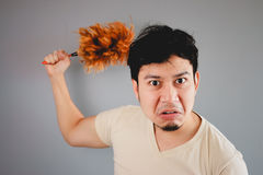 Man and feather duster. Royalty Free Stock Photos