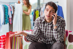 The man fed up with wife shopping in shop Stock Photography
