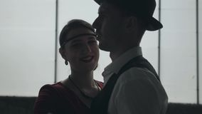 Portrait man in fedora hat, classical suits and woman in style cloth dancing in dirty place. Man in fedora hat, classical suits and woman in style cloth dancing stock video footage