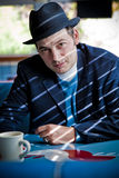 Man in Fedora Sitting in Diner. Man in black fedora sitting in diner and looking at camera. Vertical Royalty Free Stock Photography