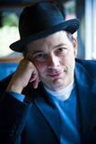 Man in Fedora Sitting in Diner. Close-up portrait of man in fedora looking at camera. vertical Royalty Free Stock Image