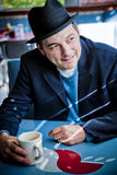 Man in Fedora Sitting in Diner. Man in black fedora sitting in diner and looking away. Vertical Stock Photography