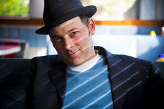 Man in Fedora Sitting in Diner. Man in black fedora sitting in diner and looking at camera. Horizontal Royalty Free Stock Photography