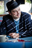 Man in Fedora Sitting in Diner. Man in black fedora sitting in diner and smiling. Vertical Stock Images