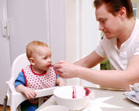 Man feeding baby Stock Image