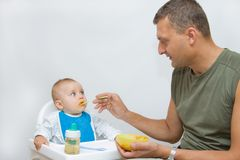 Man feeding baby with a spoon. On bright background Royalty Free Stock Image