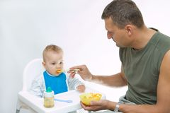 Man feeding baby with a spoon. On bright background Royalty Free Stock Photos