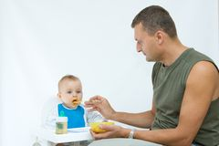 Man feeding baby with a spoon. On bright background Stock Photos