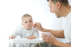 Man feeding baby with a spoon. On bright background Stock Image