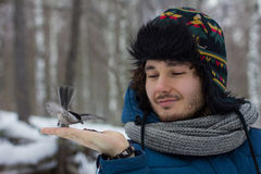 Man feeding a bird from the hand Stock Photos