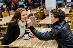 Man Feeding Biscuit To Woman At Outdoor Restaurant Royalty Free Stock Photos