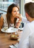 Man Feeding Bread to His Girlfriend. Portrait of a men feeding bread to his girlfriend stock photography