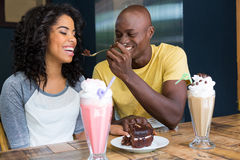Man feeding dessert to woman in coffee shop Stock Image