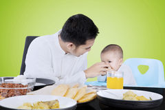 Man feeding his baby with hand. Young muslim men feeding his baby on a high chair with foods on the table, shot with green screen background Royalty Free Stock Photography