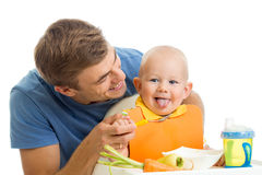 Man feeding his baby stock images