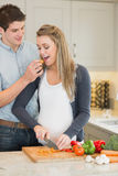 Man feeding his pregnant wife Stock Images