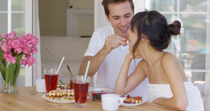Man feeding his wife fruit at breakfast Stock Photo