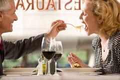 Man feeding pasta to woman Royalty Free Stock Photography