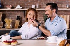 Man feeding wife with strawberry Stock Photos