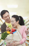 Man Feeding Woman Apple in Grocery Store Royalty Free Stock Image