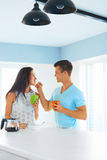 Man feeding woman in the kitchen. Handsome men feeding beautiful young women in the kitchen. Couple is drinking coffee and having fun together Royalty Free Stock Image