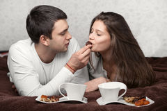 Man feeding woman. A men feeding a women on the bed Royalty Free Stock Photo