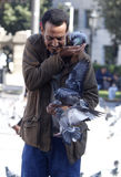 A man feeds pigeons in Catalonia square in Barcelona. Spanish local goverments punish to feed urban animal colonies such pigeons or cats Stock Photography