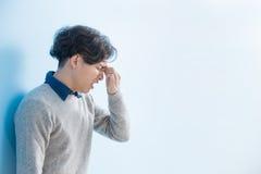 Man feel eye discomfort. Man student feel eye discomfort with isolated blue background, asian Stock Photos