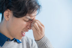 Man feel eye discomfort. Man student feel eye discomfort with isolated blue background, asian Stock Images