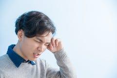 Man feel eye discomfort. Man student feel eye discomfort with isolated blue background, asian Stock Photo