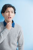 Man feel sore throat. Man student feel sore throat with blue background, asian Stock Photos