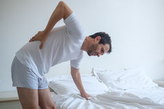 Man feeling back ache in the bed after sleeping Stock Photography