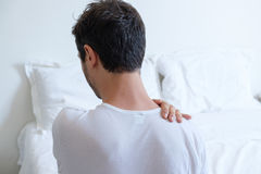 Man feeling back ache in the bed after sleeping Stock Photos