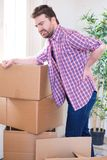 Man feeling back ache cramp moving heavy boxes. Man moving boxes and feeling back pain because heavy weight Stock Images