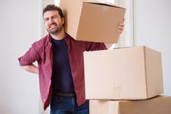 Man feeling back ache cramp moving heavy boxes Royalty Free Stock Images