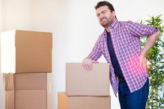 Man moving boxes and feeling back pain because heavy weight Royalty Free Stock Image