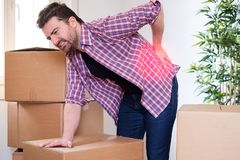 Man feeling back ache cramp moving heavy boxes. Man moving boxes and feeling back pain because heavy weight Royalty Free Stock Photography