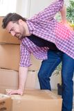 Man moving boxes and feeling back pain because heavy weight Stock Photos