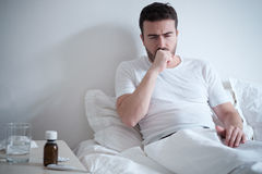 Man feeling bad lying in the bed and coughing Stock Photo