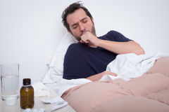 Man feeling bad lying in the bed. And coughing Royalty Free Stock Photo