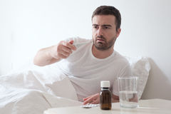 Man feeling bad lying in the bed and looking the thermometer Stock Photos