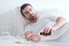 Man feeling bad lying in the bed and looking the thermometer Royalty Free Stock Photo